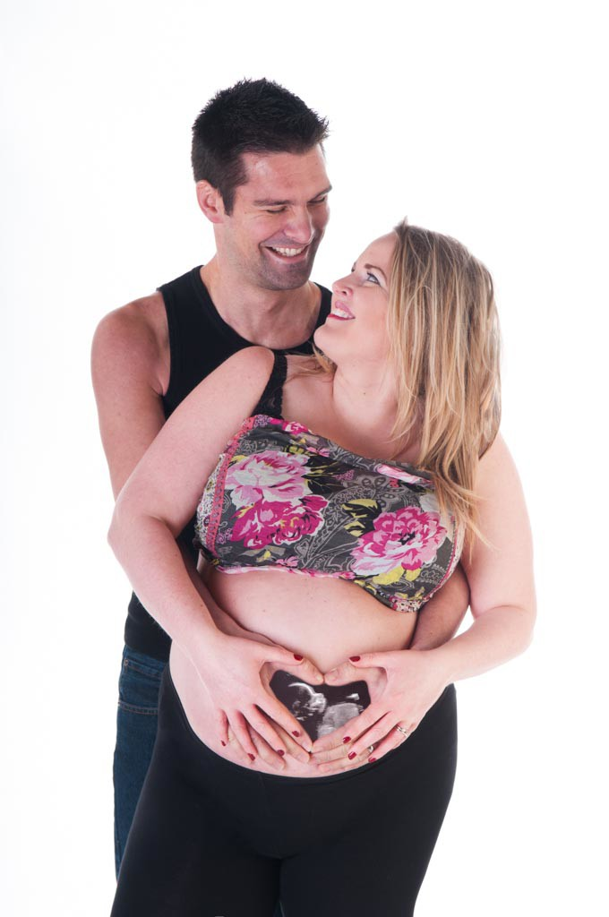 Baby scan photo inserted into hands on bump