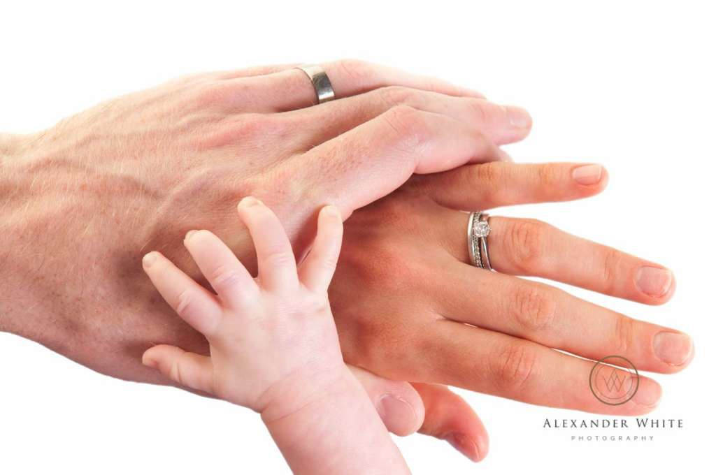 Baby Thomas' hand holding  onto his parents
