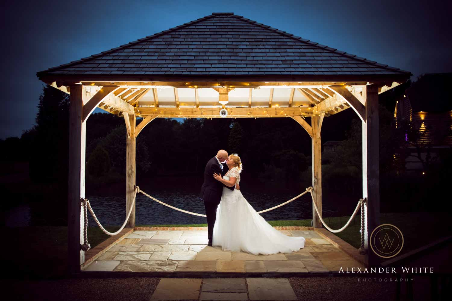 Brookfield Barn outdoor wedding venue in Horsham West Sussex Wedding photo of couple backlit under a shelter at dusk