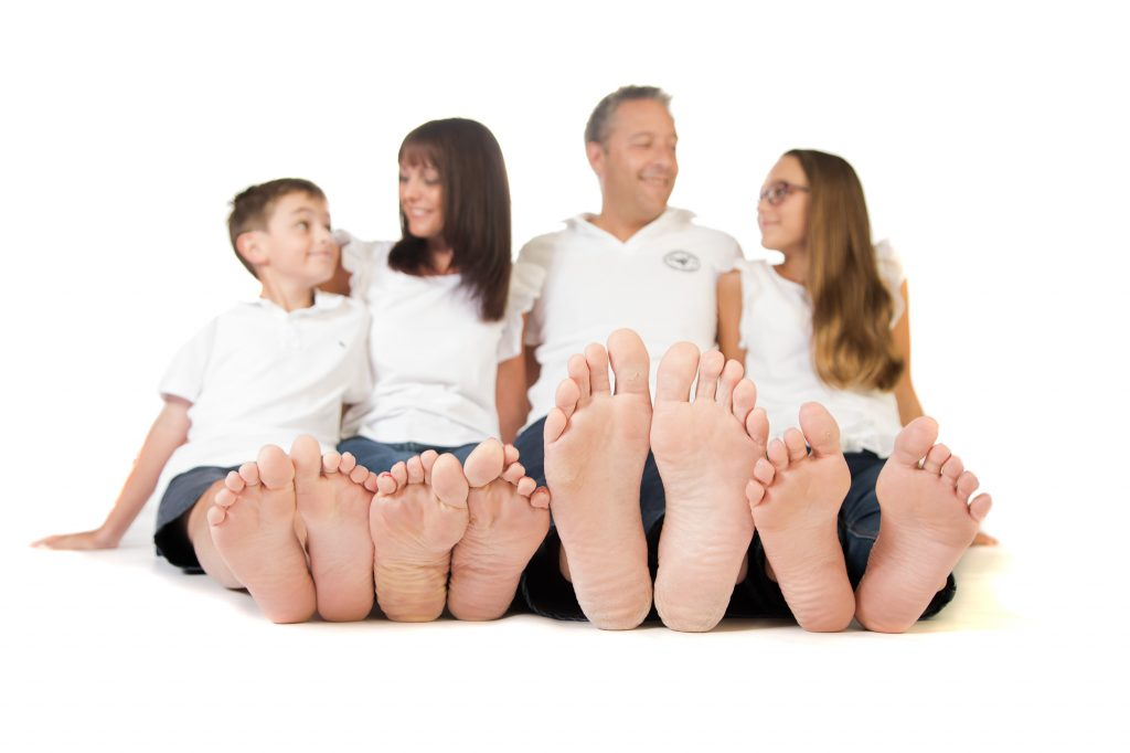A family photo of a family of four, focused on the subjects feet