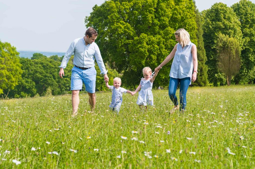 Location family portrait of a young family walking in a field of flowers