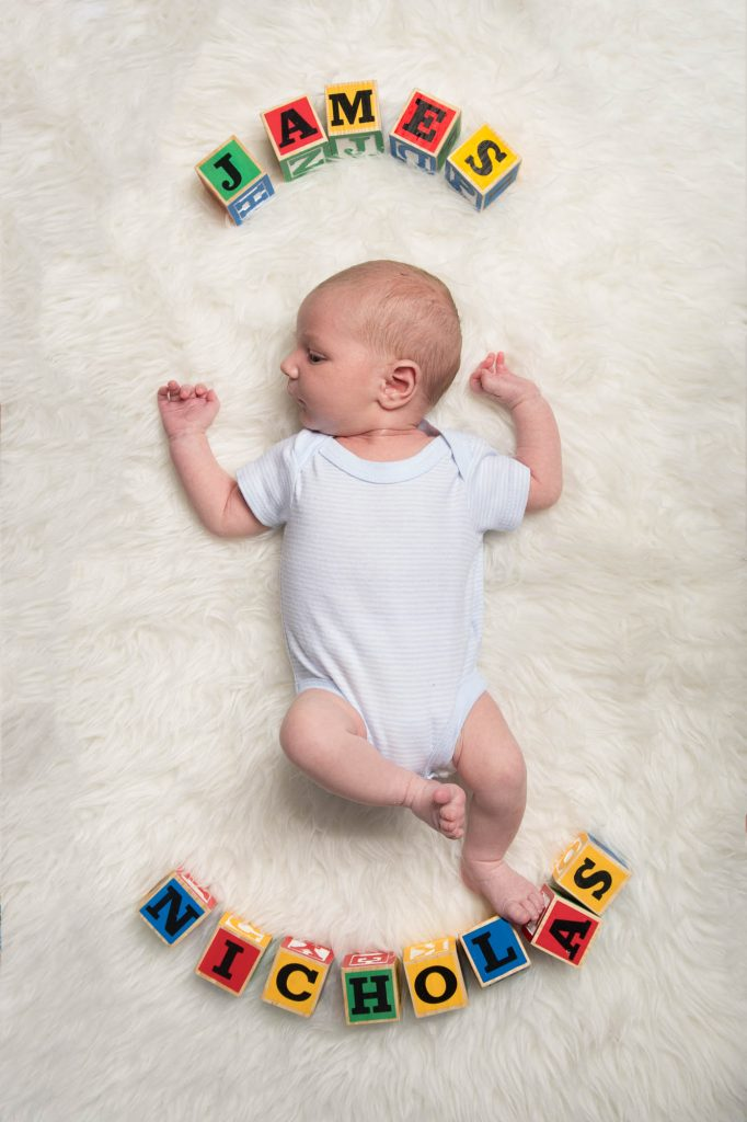 A baby with the name James Nicholas shown in alphabet blocks