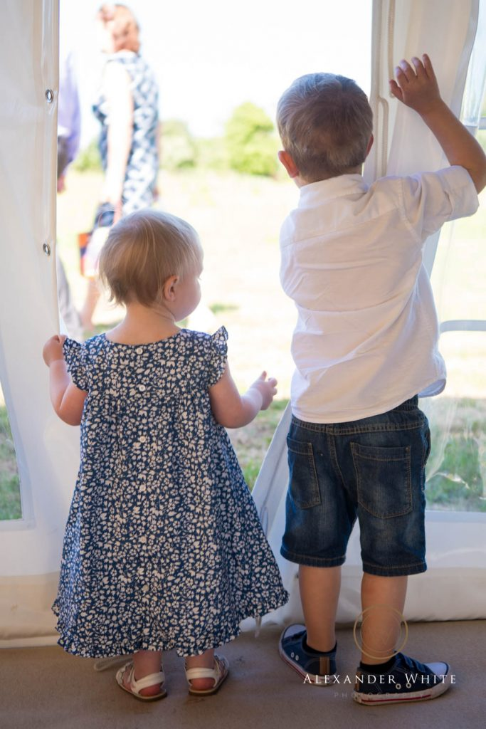 Two toddlers stand watching the goings on outside through a gap in a marquee panel.