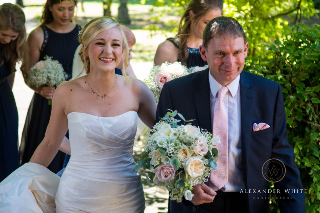 A happy bride arriving at the church with her father