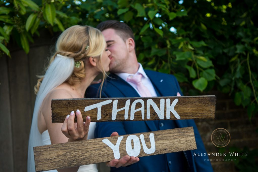Wedding photo of the bride and groom kissing whilst holding a sign saying 'Thank You'