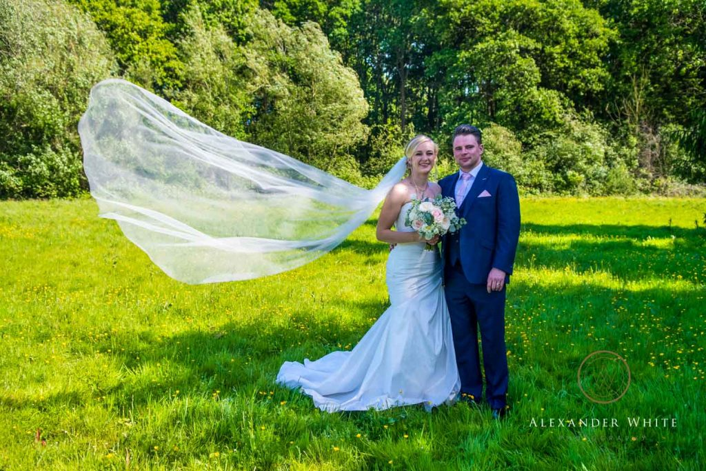 wedding photo of a bride and groom standing together with the bride's veil caught in a breeze