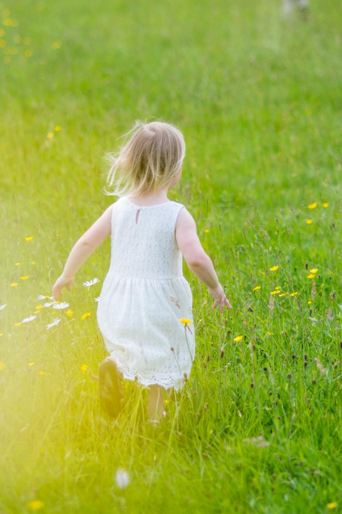 Young girl running through a field of wild flowers