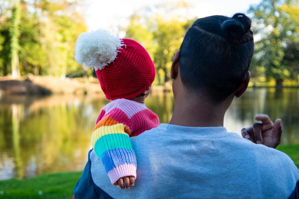 Father and baby looking out over a pond