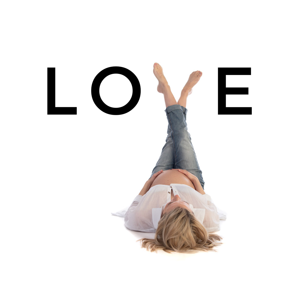 Maternity Photo of an expectant mum lying on the floor with her legs up spelling the word LOVE using her crossed legs as the letter V