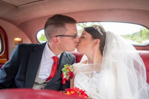 wedding photo of the bride and groom kissing in the back of a car