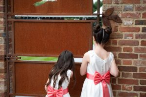 wedding photo of flower girls peeking through a door to spot their parents