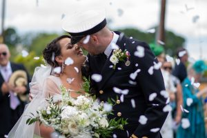 wedding photo of the bride and groom kissing surrounded by confetti