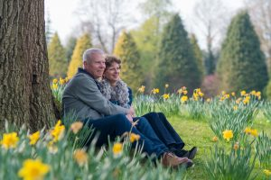 A couple sitting under a tree, surrounded by daffodils