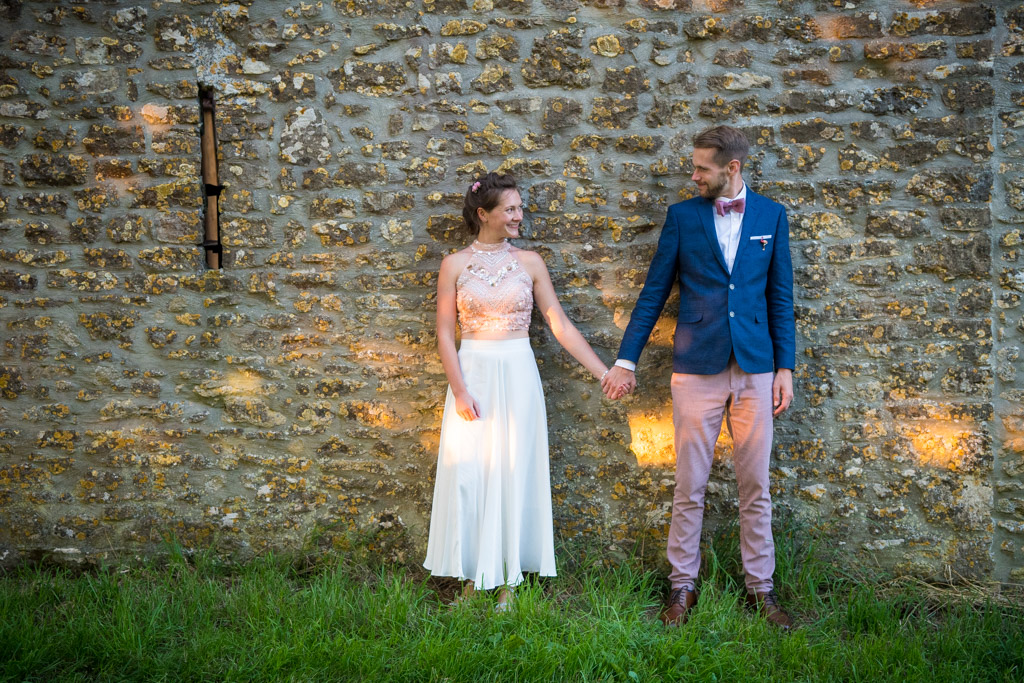 Bride and groom standing in front of a stone wall holding hands